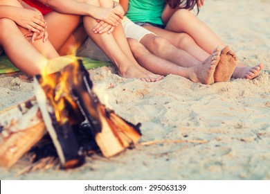 friendship, happiness, summer vacation, holidays and people concept - close up of friends sitting near fire on beach