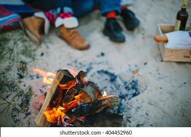 Friendship, happiness, summer vacation, holidays and people concept - Bonfire on beach and couple sitting on background out of focus.