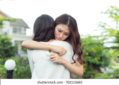 Friendship help support. Depressed asian woman embracing her friend.