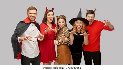 friendship, holiday and people concept - group of happy smiling friends in halloween costumes of vampire, devil, witch and leopard scaring over grey background