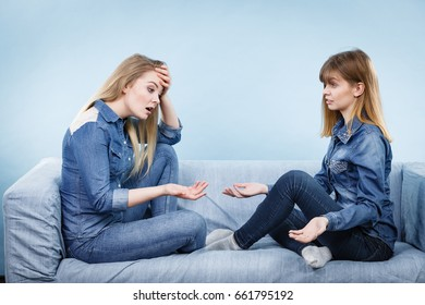 Friendship, human relations concept. Two serious women friends or sisters wearing jeans shirts having conversation, talking about solving problem.