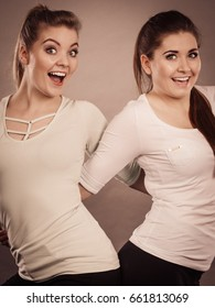 Friendship, human relations concept. Two happy women friends having fun smiling with joy wearing white tops
