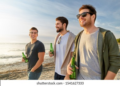 friendship and leisure concept - group of happy young men or male friends toasting non alcoholic beer walking along summer beach