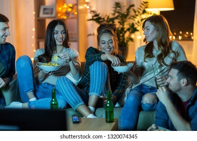 friendship, and leisure concept - happy friends with non-alcoholic drinks and snacks watching tv at home in evening