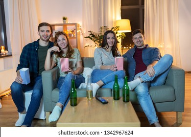 friendship and leisure concept - happy friends with non-alcoholic beer and popcorn watching tv at home in evening