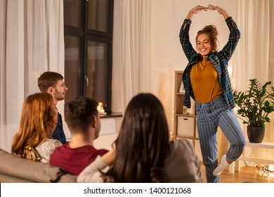 friendship, leisure and entertainment concept - happy friends playing charades game at home in evening