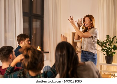 friendship, leisure and entertainment concept - happy friends playing charades game at home in evening - Shutterstock ID 1400121080