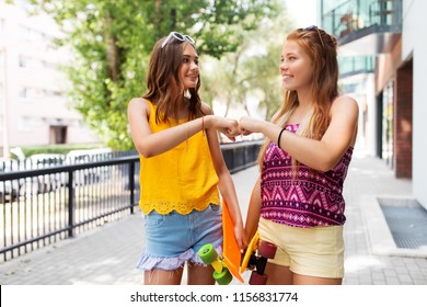 friendship, leisure and gesture concept - happy teenage girls or friends with skateboards on city street in summer making fist bump
