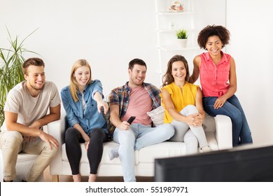 friendship, leisure, junk food, people and entertainment concept - happy friends with remote watching tv at home