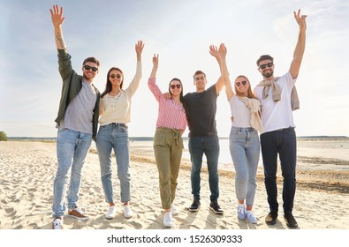 friendship, leisure and people concept - group of happy friends waving hands on beach in summer