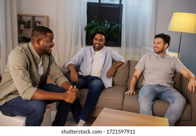 friendship, leisure and people concept - happy smiling male friends talking at home at night