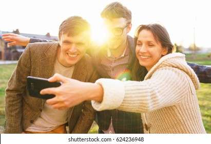 Friendship, leisure, spring, technology and people concept - smiling friends making selfie outdoors