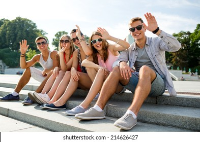 friendship, leisure, summer, gesture and people concept - group of smiling friends sitting on city street and waving hands