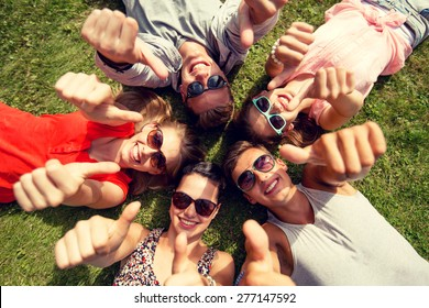 friendship, leisure, summer, gesture and people concept - group of smiling friends lying on grass in circle and showing thumbs up outdoors