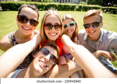 friendship, leisure, summer, technology and people concept - group of smiling friends making selfie with smartphone, camera or tablet pc in park