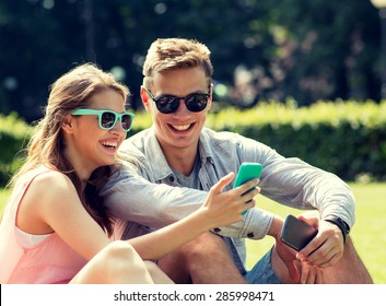 friendship, leisure, summer, technology and people concept - group of smiling friends with smartphone sitting on grass in park