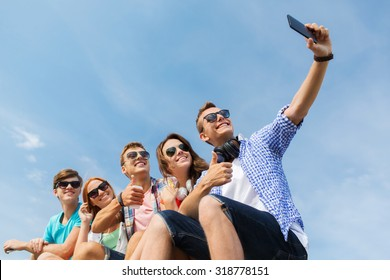 friendship, leisure, summer, technology and people concept - group of happy friends with smartphone taking selfie outdoors