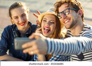 Friendship, leisure, summer, technology and people concept - smiling friends making selfie outdoors
