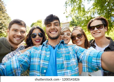 friendship, leisure and technology concept - group of happy smiling friends taking selfie at summer park