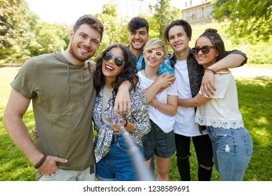 friendship, leisure and technology concept - group of happy smiling friends taking picture by selfie stick at summer park