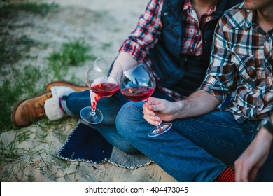 Friendship, love, happiness, summer vacation, holidays and people concept - couple sitting on beach and drinking wine from glasses near bonfire in the evening. Shallow focus.