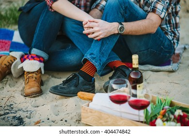 Friendship, love, happiness, summer vacation, holidays and people concept -couple sitting on beach and holding hands near bonfire. Shallow focus.
