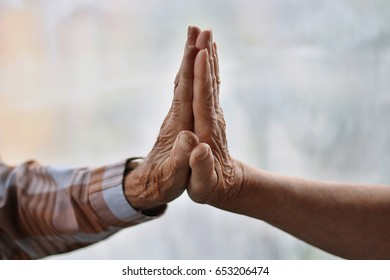 Friendship and love of senior man and elderly woman touching hands together color fog background