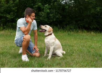 Friendship of man and dog. Happy young man sitting with his friend - dog Labrador
