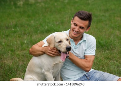 Friendship of man and dog. Happy young man is playing with his friend - dog Labrador