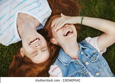 Friendship is miracle. Joyful and carefree cute redhead girls with freckles, lying on green grass and laughing out loud, woman covering eyes while chuckling, fooling around and having fun