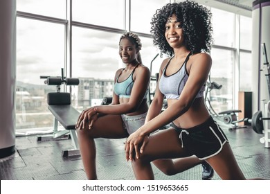 Friendship on training in gym. Two athletic afro girls doing pilates exercise. Sportive smiling black women looking camera