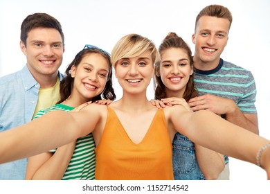friendship and people concept - group of happy smiling friends taking selfie over white background