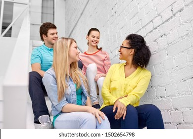 friendship and people concept - smiling teenage friends or students hanging out on stairs