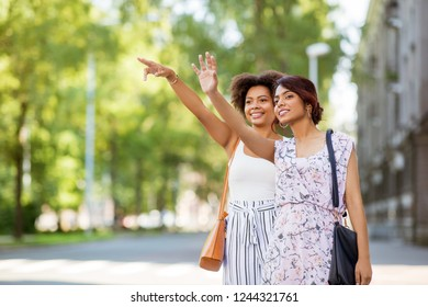 friendship, people and leisure - two happy young women or female friends catching taxi on city street in summer