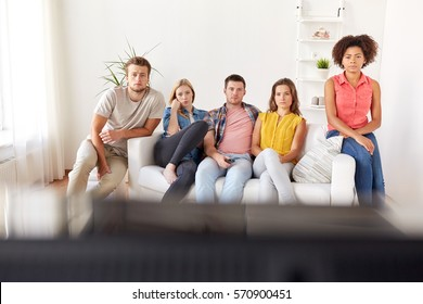 friendship, people, mass media and television concept - sad friends watching tv at home