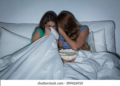 friendship, people, pajama party, entertainment and junk food concept - scared friends or teenage girls eating popcorn and watching horror movie on tv at home