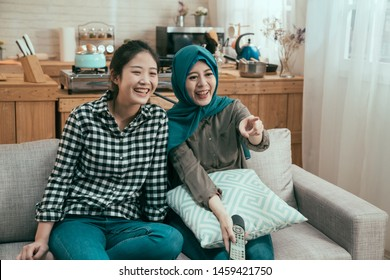 friendship people party entertainment concept. happy multi ethnic friends watching movie on tv at home. group of chinese and muslim women laughing and point at television screen while enjoy series.