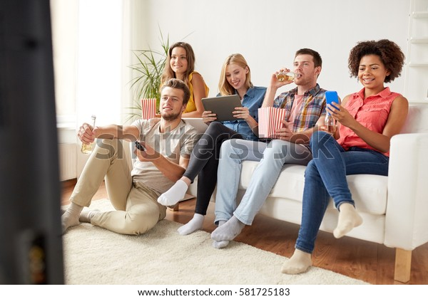 friendship, people, technology and entertainment concept - happy friends with tablet pc computer and smartphone eating popcorn, drinking beer or cider and watching tv at home