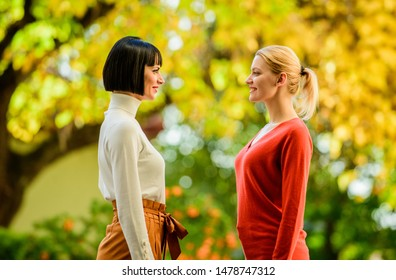 Friendship problems rivalry and jealousy. Rivalry and leadership. Pretty girls friends sisters. Eye contact. Women looking at each other with attention. Blonde brunette competitors.