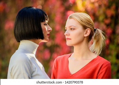 Friendship problems rivalry and jealousy. Pretty girls friends sisters. Eye contact. Women looking at each other with attention. Rivalry and leadership. Blonde brunette competitors. Female rivalry.