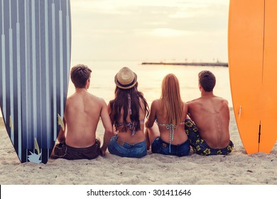 friendship, sea, summer vacation, water sport and people concept - group of friends wearing swimwear sitting with surfboards on beach from back