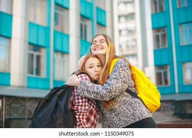 Friendship and sisterhood concept. Student sisters hugging each other. Two happy affectionate girls hugging each other in a close embrace while laughing and smiling. Young reddish hair female friends.