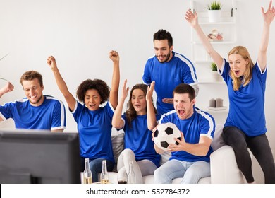 friendship, sport, people and entertainment concept - happy friends or football fans watching soccer and celebrating victory at home