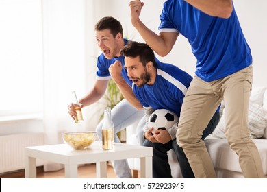 friendship, sport, people and entertainment concept - happy male friends or football fans watching soccer at home