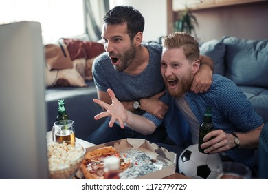 Friendship, sport, people and entertainment concept-happy male friends  watching soccer on tv at home.