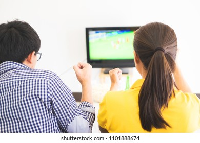 friendship, sports and entertainment concept - happy male friends cheering and watching tv together at home supporting world cup football team win.