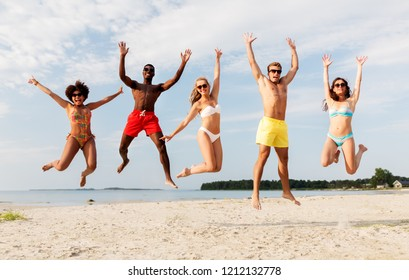 friendship, summer holidays and people concept - group of happy friends jumping and having fun on beach