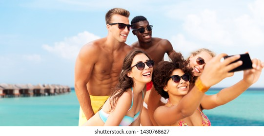 friendship, summer holidays and people concept - group of happy friends taking picture by smartphone over tropical beach background in french polynesia
