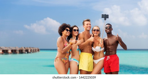friendship, summer holidays and vacation concept - group of happy friends taking picture by smartphone on selfie stick and showing thumbs up over tropical beach background in french polynesia