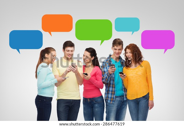 friendship, technology, communication and people concept - group of smiling teenagers with smartphones over messenger text bubbles and gray background